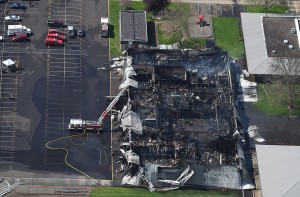 A lone Albany Fire Department ladder crew stands vigil over the smoldering remains of South Albany high school's cafeteria, Wednesday, April 1, 2015 in Albany, Ore. (AP Photo/Albany Democrat-Herald, Mark Ylen)